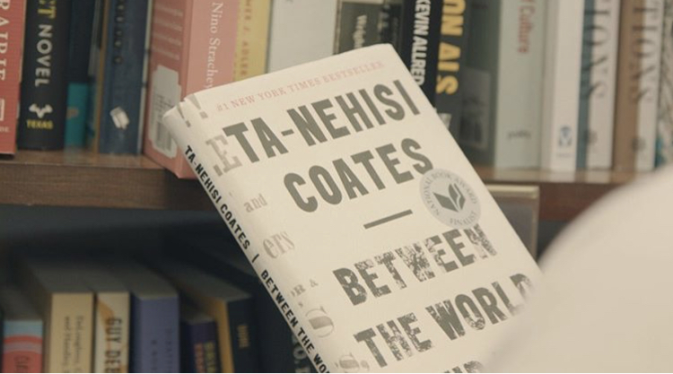 A copy of Ta-Nehisi Coates' Between the World and Me against a backdrop of books on shelves